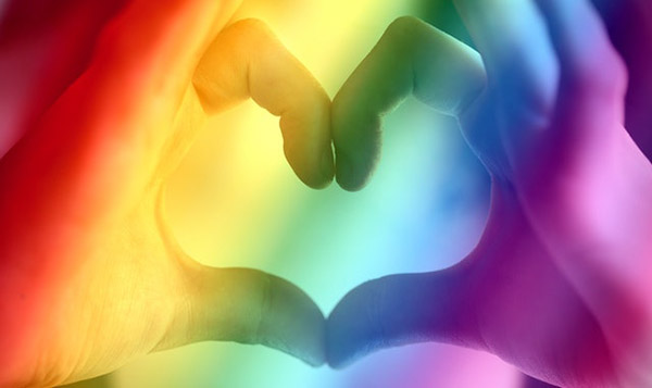 Hands form a heart with a rainbow cover overlay