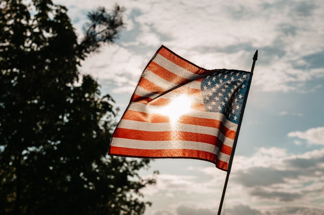 american flag waving in front of the sun